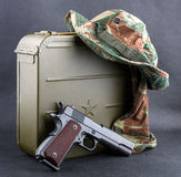 Box for bullets, a gun and a camouflaged hat. Royalty Free Stock Photos