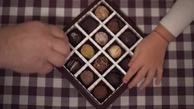 The box of candies stands on the table. Four hands taking sweets one by one. Children and grandparents eat chocolate at. Home. Leisure of happy family stock video footage