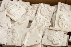 Box of ceramic tiles ready to be glazed. WREXHAM, UNITED KINGDOM - MARCH 14, 2016: Box of ceramic 'mini beasts' tiles ready to be glazed. Part of a workshop Stock Photo