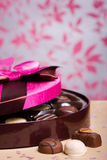 Box of chocolates. Luxury chocolates in a box with pink satin lid, shallow depth of field with focus on chocolates at front Royalty Free Stock Image