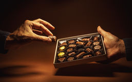Box Chocolates in Hands. Male hands are holding an open box of chocolates and pick one Stock Photo
