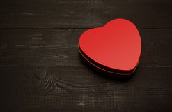 A box of chocolates in a heart. On a dark wooden background Stock Image