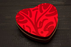 A box of chocolates in a heart. On a dark wooden background Royalty Free Stock Photos