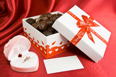 Box of chocolates with opened box for a rings. Box with chocolate and present on the red background Royalty Free Stock Photography