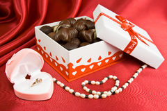 Box of chocolates with present and pearls. Box with chocolate and present on the red background Stock Photography