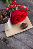 Box of chocolates, red rose on a dark background Stock Photo