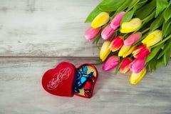 Box of chocolates and tulips Stock Photos