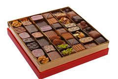 Box of chocolates. Variety of luxury chocolates on gold red box isolated Royalty Free Stock Images