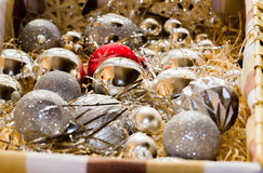 Box with Christmas bulbs. Box full of sparkling silver (one is red) Christmas bulb, straw and gleaming gold and silver stripes Royalty Free Stock Photos
