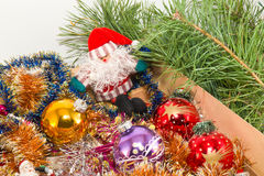 Box with Christmas decorations. The box with the Christmas decorations on the background of Christmas tree branches Royalty Free Stock Photography