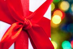 Box with Christmas gift with red bow and Christmas bokeh light abstract holiday background.  Royalty Free Stock Images