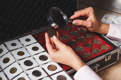 Box with collectible coins in the cells. And a hand with coin through the magnifying glass, soft focus background Stock Photos