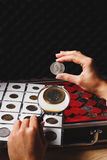 Box with collectible coins and magnifying glass. Box with collectible coins in the cells and a page with coins in the pockets, soft focus background Stock Photos