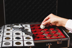 Box with collectible coins and magnifying glass. Box with collectible coins in the cells and a page with coins in the pockets, soft focus background Royalty Free Stock Photo