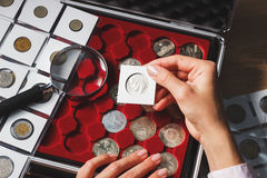 Box with collectible coins and magnifying glass. Box with collectible coins in the cells and a page with coins in the pockets, soft focus background Royalty Free Stock Photos