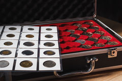 Box with collectible coins and a page with coins. Box with collectible coins in the cells and a page with coins in the pockets, soft focus background Royalty Free Stock Photos