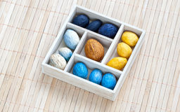 Box with colored nuts on a bamboo napkin Stock Photos