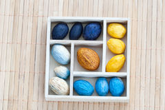 Box with colored nuts on a bamboo napkin Royalty Free Stock Photos