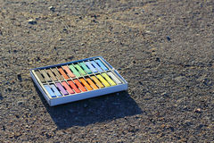 Box of colorful crayons, chalk on the asphalt. Stock Photos