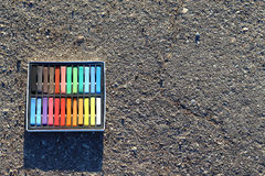 Box of colorful crayons, chalk on the asphalt. Stock Image