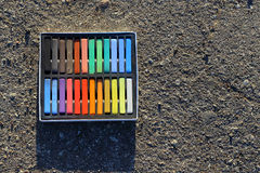 Box of colorful crayons, chalk on the asphalt. Stock Photo
