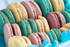 Box of colorful French Macarons. Assortment of fresh french macarons packaged in a pretty blue paper with blurred  background royalty free stock photo