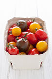 Box with colorful tomatoes. On white table Stock Images