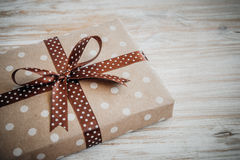 Box in craft paper, eco paper on the wooden table. Top view. Brown paper wrapped gift box with satin ribbon bow on a old. Rustic wooden background. Background Royalty Free Stock Photography
