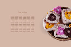 Box of crocheted square pattern motives on beige background Royalty Free Stock Photography