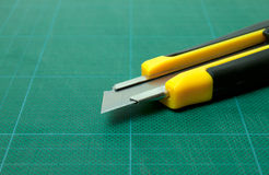 Box cutter and cutting mat. Box cutter placed on green cutting mat Royalty Free Stock Images