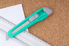 Box cutter, Ruler and Paper on a Cork Board Stock Image