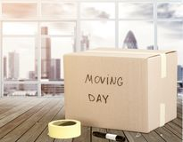 Cardboard Box labelled moving day on backgrouund. Box day cardboard moving cardboard box moving day white Royalty Free Stock Images