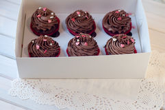 Box with delicious chocolate cupcakes lay on white serviette on wooden table Stock Photography