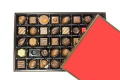 Box of delicious chocolates box with red lid isolated on white background. Stock Photos
