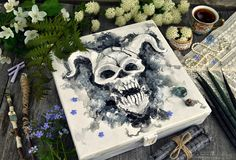 Box with devil face and magic objects with flowers. Occult, esoteric and divination still life. Halloween background with vintage objects and magic ritual royalty free stock image