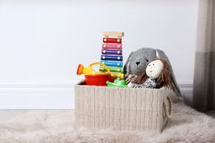 Box with different child toys on floor against white wall. Space for text royalty free stock photography