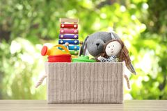 Box with different child toys on table. Against blurred background stock photo