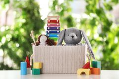 Box and different toys on table. Against blurred background royalty free stock images