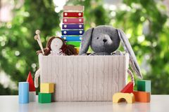 Box and different toys on table. Against blurred background stock images