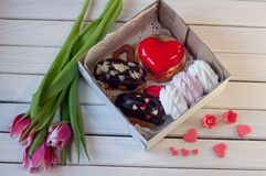 Box with eclairs, marshmallow, cake lay on wooden table near tulips Stock Images