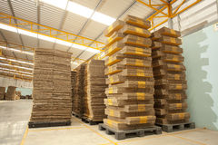 Box factory. Folded brown cardboard box indoor yellow factory building Royalty Free Stock Photography