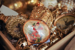 Box filled gold christmas decorations and  ball with st nicolas picture Royalty Free Stock Images