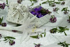 The box is filled with purple flowers on the surface covered Royalty Free Stock Photo
