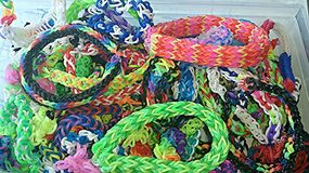 A box filled with rainbow loom bracelets Royalty Free Stock Photography