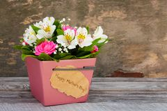 Box with flowers on old wooden background. Royalty Free Stock Image