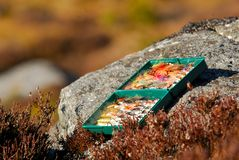 Fishing Tackle Box of fly fishing flies on a riverbank rock Stock Photo