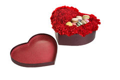 The box in the form of heart, is filled by flowers and cookies. Stock Photos