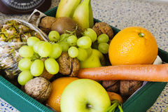 Box of fruit and vegetables on the kitchen table. Royalty Free Stock Photos