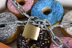 Box full of tempting delicious donuts wrapped in metal chain and lock in sugar and sweet addiction Stock Images