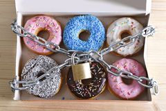 Box full of tempting delicious donuts wrapped in metal chain and lock in sugar and sweet addiction. And diet body and dental care concept Stock Photography